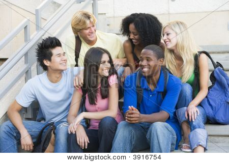 Six People Sitting On Staircase Outdoors Smiling
