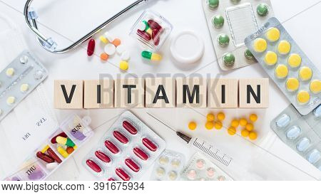 Vitamin Medicine Word On Wooden Blocks On A Desk. Medical Concept With Pills, Vitamins, Stethoscope