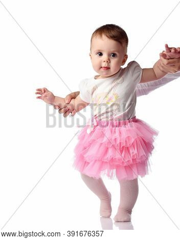 Cute Little Infant Baby Girl Learning To Walk Doing First Step With Mom Hand Support. Mother Teachin