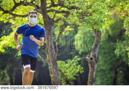 Young Man In Face Mask And Jogging In The Park During Quarantine