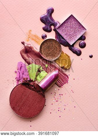 Set Of Makeup Products On A Pink Background. Abstract Composition Of Spilled And Scattered Makeup Te