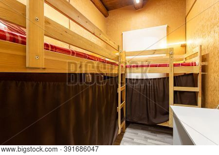 Wooden Bunk Beds With Curtains In A Large Hostel Dorm Room
