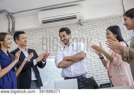Team Of Business Applauding Their Leader After Success On Business In Office And Discussing Document