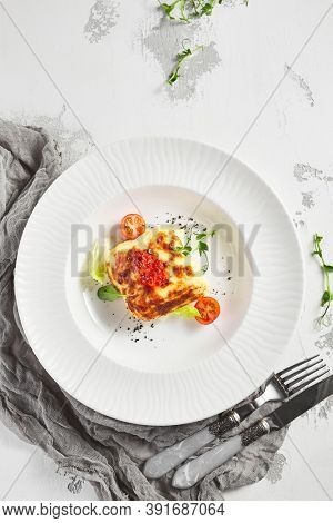 Lasagna with tomato and green leaf. Fish with bechamel sauce. White restaurant plate on light table