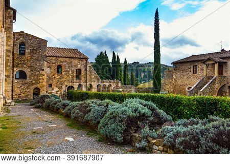 Medieval magnificent abbey of San Antimo. Green park around the abbey. Picturesque Tuscany. The concept of active, rural and photo tourism