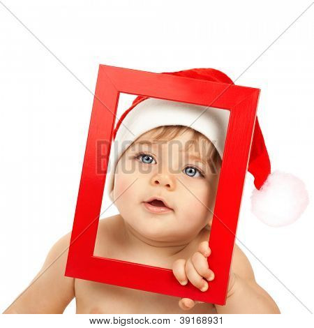 Image of adorable kid wearing funny Santa Claus hat, Christmas angel, nice little baby boy with blue eyes isolated on white background, curious child looking from red frame, New Year concept