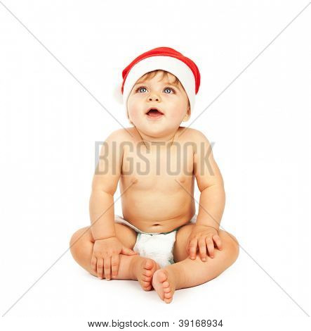 Photo of little baby boy wearing Santa Claus hat, small cute child sitting in diaper isolated on white background, lovely infant celebrate Christmas eve, New Year holiday, happiness concept