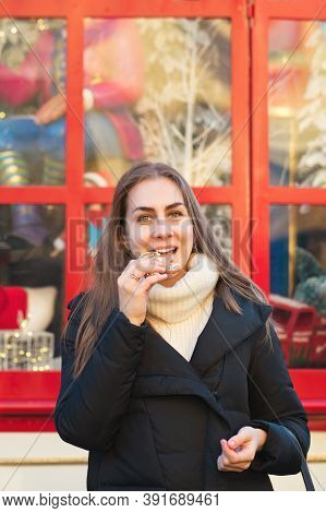 Cheerful Young Woman Posing With Gingerbread At Christmas Market. Merry Christmas And Happy Holidays