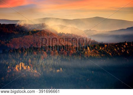 Dramatic Autumn Dawn In Mountains. Beautiful Nature Background. Fog Above The Forested Hills In Red