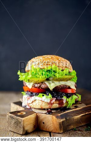 Big Burger On A Dark Background. Beef Burger. Delicious Burger With Sauce. Hamburger. Delicious Gril