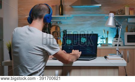 Back View Of Hacker With Headset Attacking Succesfully The Government Using Finetech, Working From H