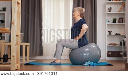 Old Woman Workout On Training Ball In Living Room. Old Person Training Home Healthy Retirement Lifes