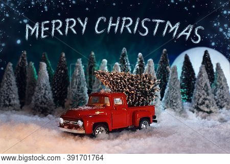 Merry Christmas toys greeting card. A red toy pick-up truck in a snowy spruce forest is driving a Christmas tree home. There is a large moon and northern lights in the night sky.