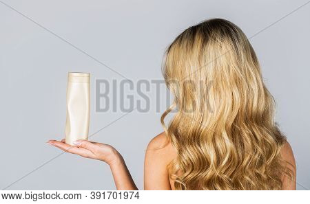 Woman Hold Bottle Shampoo And Conditioner. Woman Holding Shampoo Bottle. Beautiful Blonde Girl With