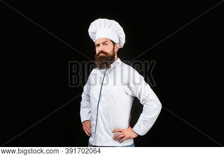 Serious Cook In White Uniform, Chef Hat. Portrait Of A Serious Chef Cook. Bearded Chef, Cooks Or Bak