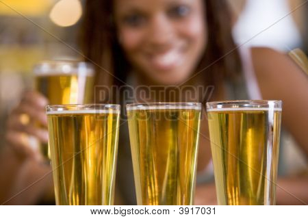 Woman posing with several beer glasses poster