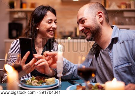 Cheerful Couple Laughing Using Smartphone During Relationship Anniversary. Adults Sitting At The Tab