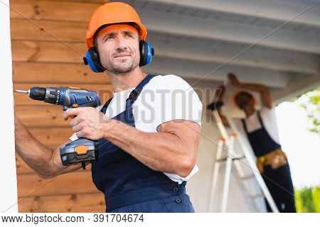 Selective Focus Of Handyman In Workwear And Ear Defenders Holding Electric Screwdriver Near Facade O
