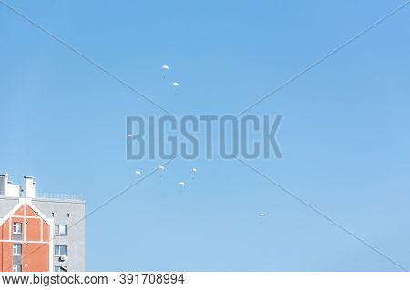 The White Parachute In The Blue Sky. A Group Of Paratroopers Perform Exercises Over The City. The Cl