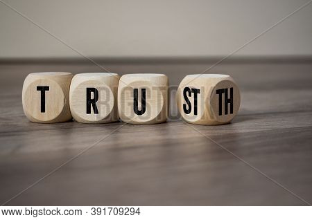 Cubes, Dice Or Blocks With Trust And Truth On Wooden Background