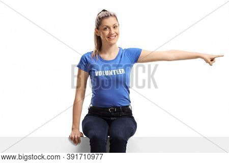 Young female volunteer sitting on a white panel and pointing in one direction isolated on white background