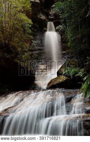 Waterfall Flowing Out Of A Canyon Into A Gorgw Ravine In Blue Mountains