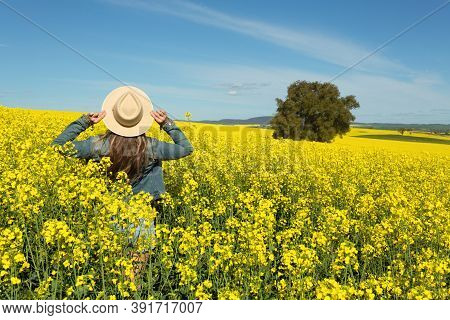 Female In Denim Jacket And Shorts  In A Field Of Flowering Canola Growing In Rural Outskirts Of Aust