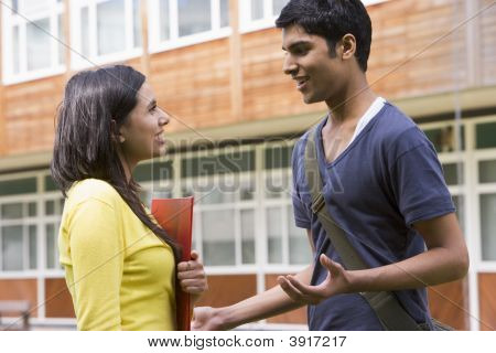 Two Students Standing Outdoors Smiling And Talking