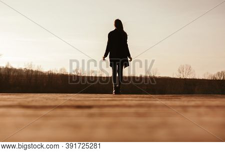 Back View Silhouette Of Unrecognizable Female In Warm Clothes Walking Alone On Dry Grassy Meadow In