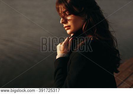 Side View Of Pensive Lonely Female In Warm Coat Contemplating While Resting Alone Near River Water I