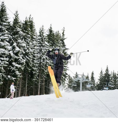 Male Skier Skiing On Fresh Powder Snow With Snowy Pine Trees On Background. Man Freerider Holding Sk
