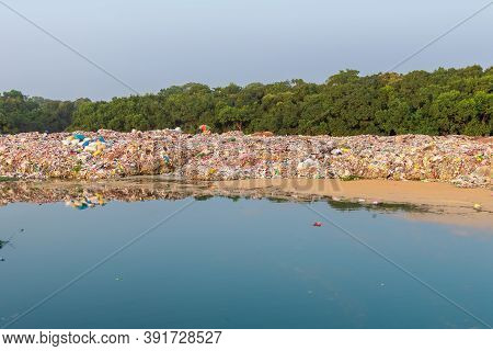 Waste Garbage Landfill. Heap Of Garbage At A Junkyard Near The River. Water And Land Pollution.