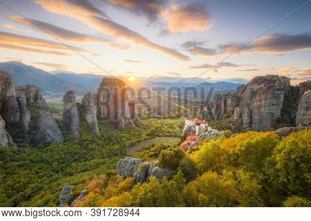 Panoramic landscape of Meteora, Greece at romantic sundown time with real sun and sunset sky. Meteora - incredible sandstone rock formations.  The Meteora area is on UNESCO World Heritage