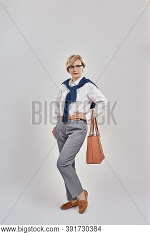 Full Length Shot Of Elegant Middle Aged Caucasian Woman Wearing Business Attire And Glasses Looking