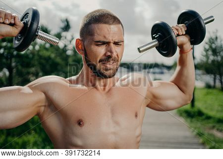 Sporty Determined Muscular European Man Exercsises With Dumbbells, Makes Weightlifting Outdoor, Has