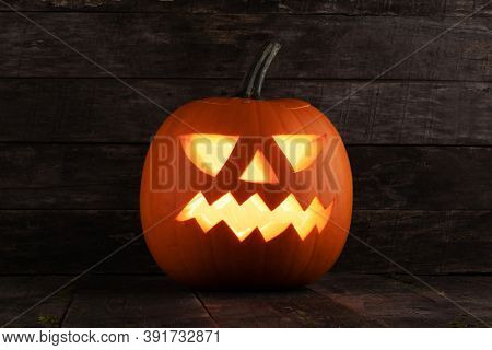 Carved jack-o-lantern halloween pumpkin on wooden background