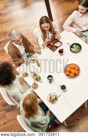 Business Lunch. A Group Of Five Creative Women Of Different Age Well-dressed Sitting At A Tablke Tog