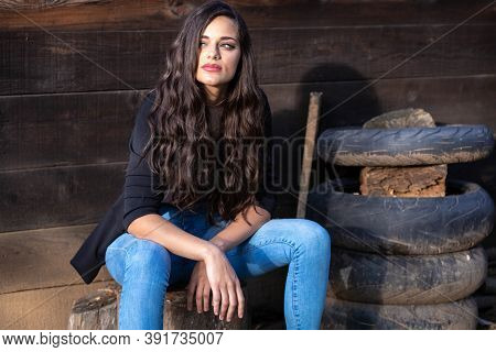 Portrait Of A Beautiful Brunette Girl In Jeans, Sitting Next To A Pile Of Old Tires
