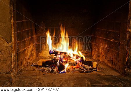 Old Stone Fireplace With Burning Wood, Embers And Bright Fire