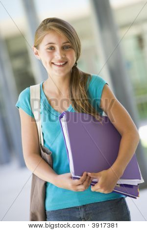 Student Standing Outside School With Binder Smiling (Selective Focus)
