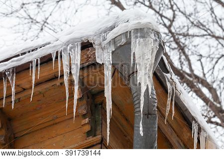 Frozen Mansion With Water Pipe And Frozen Icicles On The Roof. Icy Weather Winter Scene.