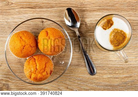 Orange Muffins In Plate, Teaspoon, Transparent Glass Cup With Latte-macchiato On Wooden Table. Top V