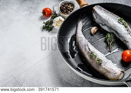 Whole Fish Pollock In A Pan. Raw Seafood. White Background. Top View. Copy Space