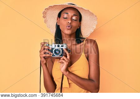 Young african american woman wearing summer hat holding vintage camera looking at the camera blowing a kiss being lovely and sexy. love expression.