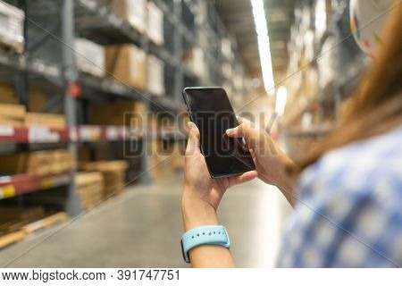 Young Modern Woman Using Touch Screen Mobile Phone In Warehouse Storage. Asian Girl Hold Cell Phone