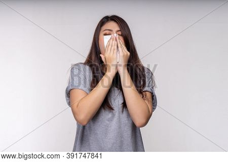 Woman With Allergy Sneezing On Napkin Paper With White Background. Sick Young Asian Woman With Fever