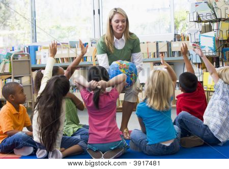 Teacher In Class With Students Volunteering