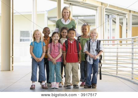Seven Students Standing With Teacher Outdoors At School