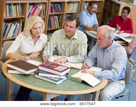 Three People In Library With Notepads (Selective Focus)