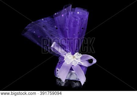 Wrapped chocolate candy on black background, sweet gift